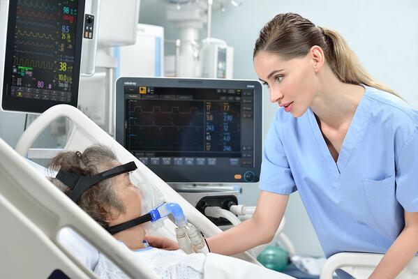 Nurse at patient bedside considers pressure injury prevention and treatment options for patient with head in brace on oxygen